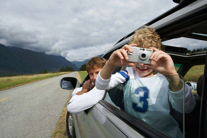 Boy in back seat of a car taking photo's out the window and smiling